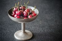 Fresh cherries in vintage silver vase