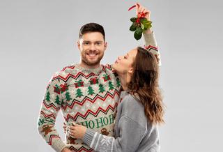 happy couple kissing under the mistletoe