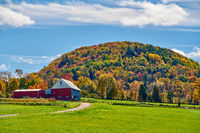 Farm with red barn at sunny autumn day