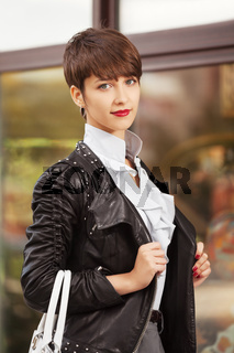 Happy young fashion woman in leather jacket with handbag next to mall window
