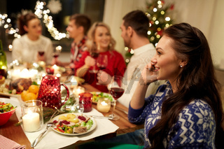 woman calling on smartphone at christmas dinner