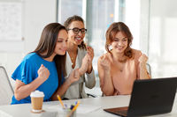 happy businesswomen with laptop at office