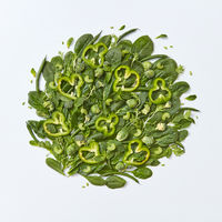 Different green vegetables broccoli, spinach, brussels sprouts, asparagus, mint leaves, cucumber and pepper slices on a gray background with space for text. Healthy food concept. Flat lay