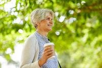 senior woman drinking takeaway coffee at park