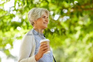 senior woman drinking takeaway coffee at park