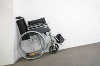 folded wheelchair at a white wall