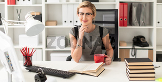 A young girl is sitting at a table in the office, holding a pencil and a red cup in her hand. Before the girl lies an open book.