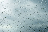 Textured background of window panes with a cloudy background. Natural pattern from a drop of rain on a cloudy background.