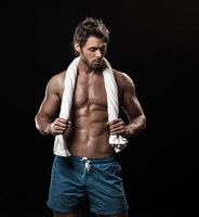 Muscular man posing with towel
