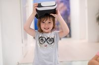 little girl at home wearing vr glasses