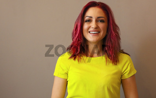 Portrait of a woman with pink hair wearing yellow dress on a wall background