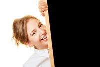 Junge Frau schaut hinter Kreidetafel hervor
