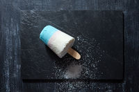 Multicolored ice cream on a stick with coconut crumb represented on a black slate on a dark concrete background with copy space. Flat lay