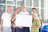 Gruppe Senioren hält leeres Plakat im Fitnesscenter