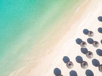 Aerial view of amazing tropical white sandy beach with palm leaves umbrellas and turquoise sea.
