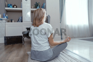 Back of mature woman sitting in lotus pose.