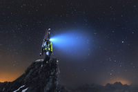 Night landscape. A professional backcountry skier with a backpack and skis stands on a rock in the mountains and shines headlamp into the sky