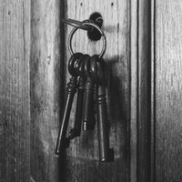 Old rusty keys inside a keyhole of an old antique closet. vintage design black and white