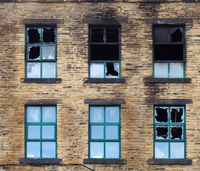 broken windows in a large burned out old industrial building after a fire