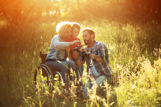 Photographer takes pictures of happy family where woman is in a wheelchair