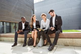 Business Team sitzt vor dem Büro Gebäude