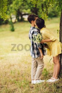 Little girl kissing boy.