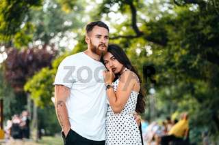 Handsome guy hugging his girlfriend in the park.