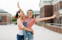 teenage girls or friends in headphones in city