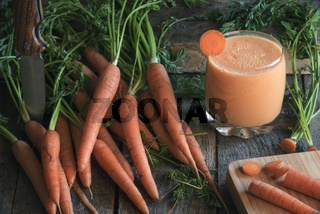 Bundle of carrots and a glass of fresh juice