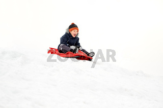 happy boy sliding on sled down snow hill in winter