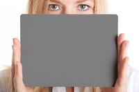 Blonde woman holding a grey card in her hands. Photography, videography and advertising concept.