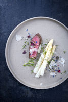 Modern Italian barbecue dry aged tagliata di manzo with white asparagus and parmesan as top view on a plate