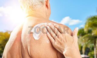 Senior Mann mit Sonnencreme am Rücken