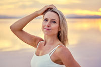 Middle-aged sportive woman posing during sunset on nature