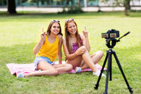 teenage bloggers recording video by camera in park