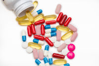 Assorted pharmaceutical medicine pills, tablets and capsules and bottle on white background. Copy space for text