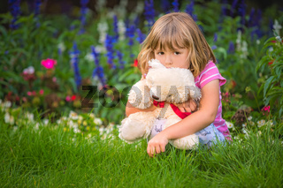 Adorable girl hugging her teddy bear in summer park