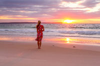 Woman standing on the wet sand of the beach watching sunrise