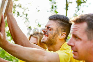 Junger Mann drückt gegen ein Holzbrett