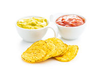 Corn nacho chips with avocado and tomato dip. Yellow tortilla chips and guacamole salsa.
