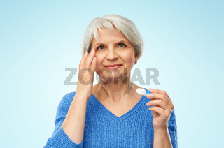 senior woman applying contact lenses over blue
