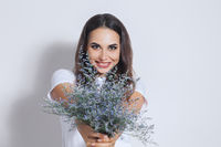 Happy positive young woman with bouquet of wild flowers over white background