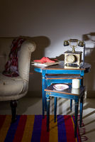 Old telephone set, red starfish and colorful ornate plate over nested tables, colorful Capet, and cream armchair with harsh light