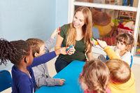 Kindergärtnerin und Gruppe Kinder mit Knete