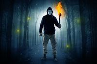 Man coming from dark forest with burning flambeau in his hand concept