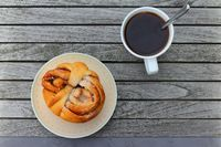 Cup of coffee and bun with cinnamon