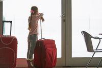 Kleines Mädchen im Flughafen mit Koffer reist alleine