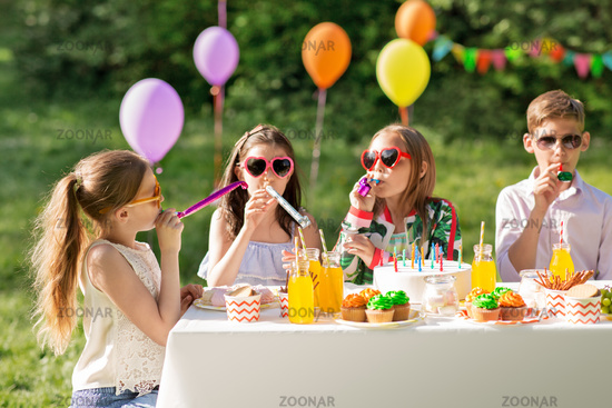 happy kids blowing party horns at summer birthday