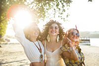 Happy slim tan women on the beach in sunset. Travel and happiness concept