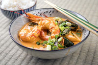 Traditional Thai kaeng phet red curry with king prawns and rice as top view in a bowl on place mat